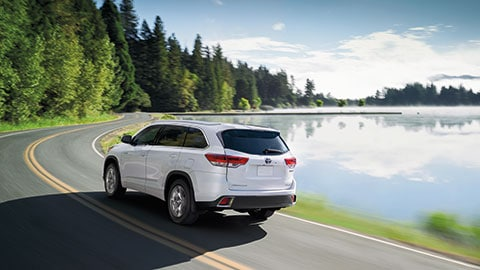 A white 2019 Toyota Highlander driving around a lake