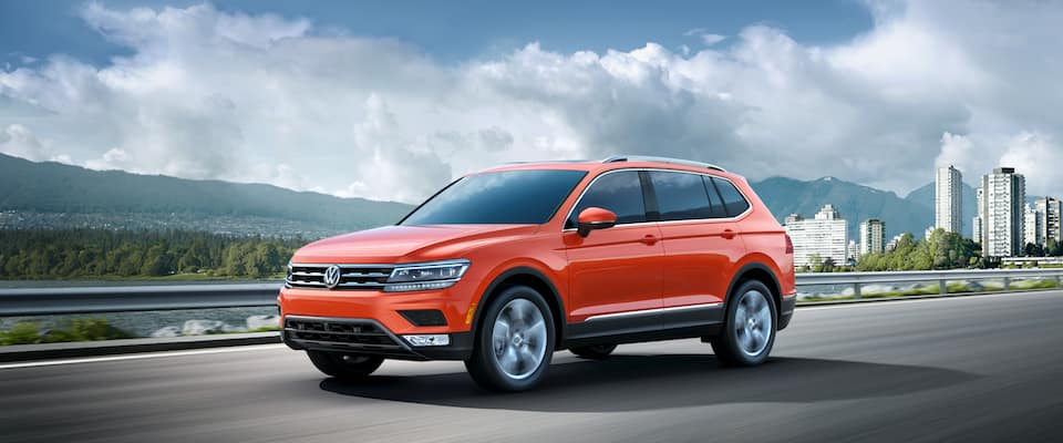 An orange 2019 VW Tiguan driving out of a city