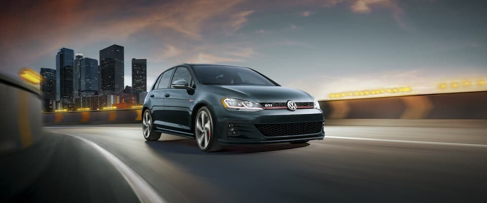 A black 2019 VW Golf GTI driving out of the city