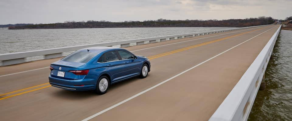 A blue 2019 VW Jetta driving down a bridge