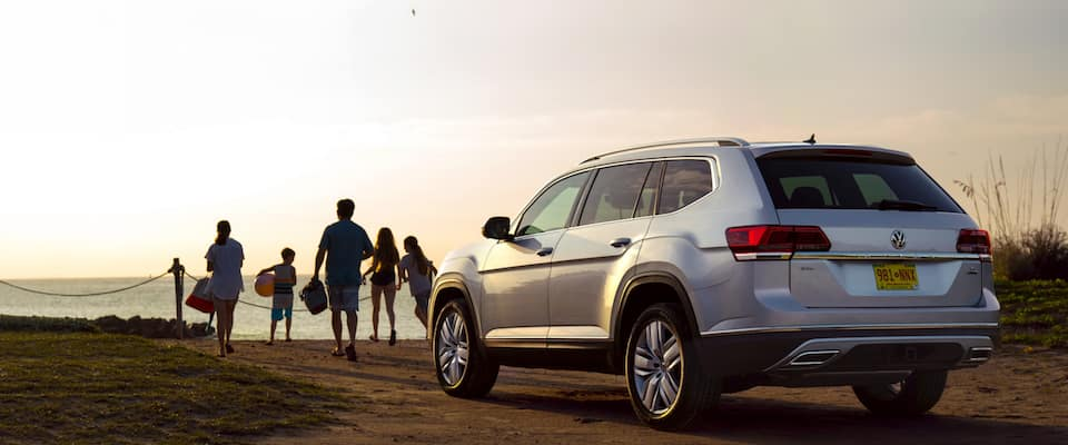 A silver 2019 Volkswagen Atlas parked on the beach at sunset