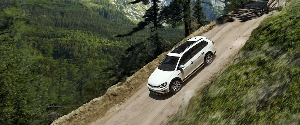 A white VW Golf Alltrack driving down a dirt hill