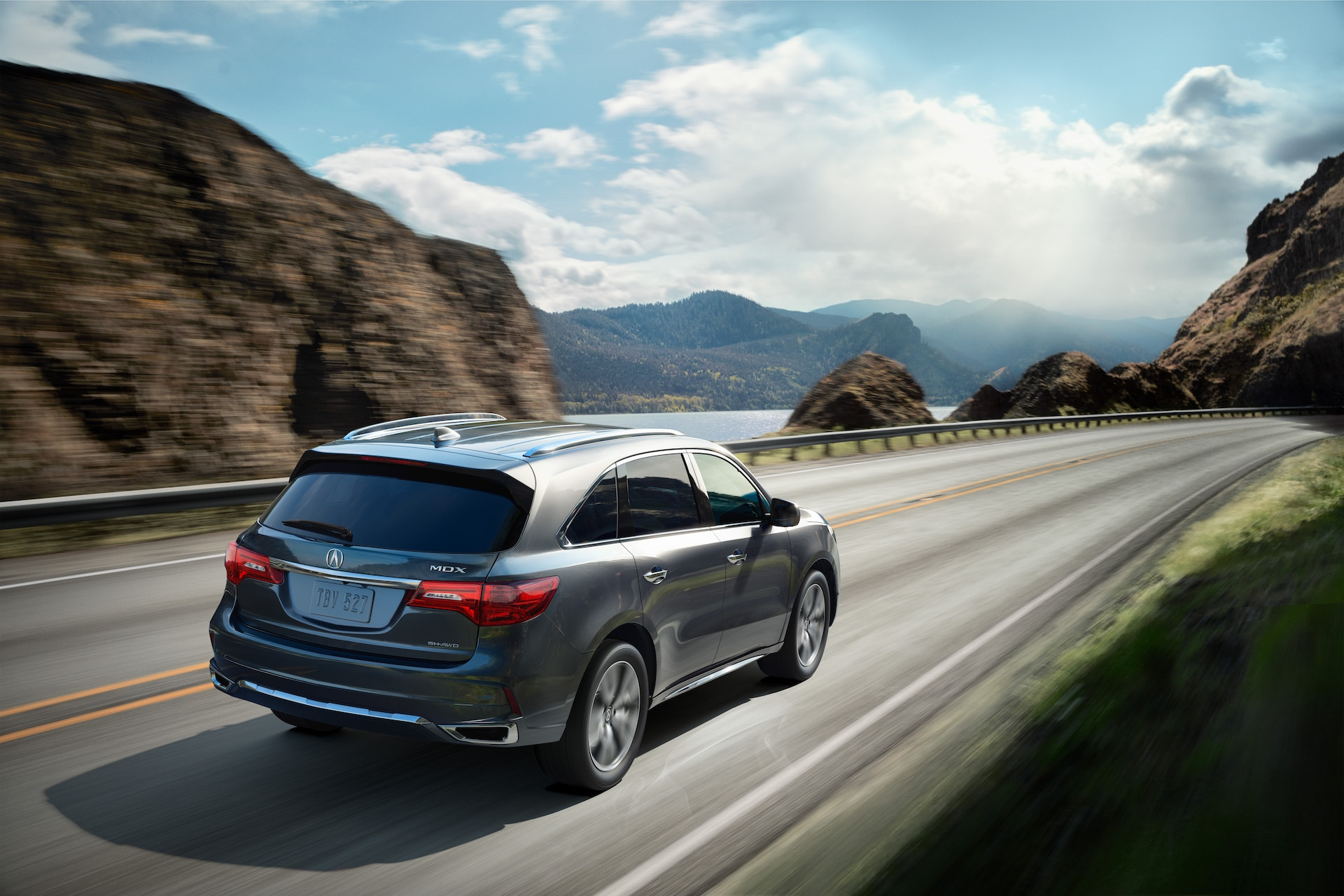 Compare the 2020 Lexus RX & the 2020 Acura MDX at Acura Hunt Valley | Gray 2020 Acura TMDX speeding away from camera on sea cliff road