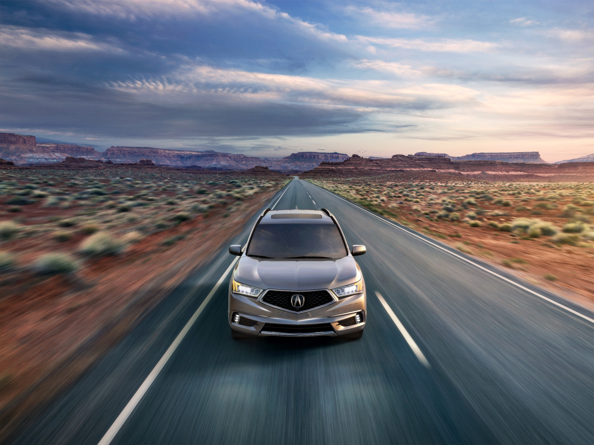 Comparison of the 2020 Acura MDX & 2020 Toyota Highlander at Acura Hunt Valley | Grey 2020 Acura MDX driving on desert road at sunset