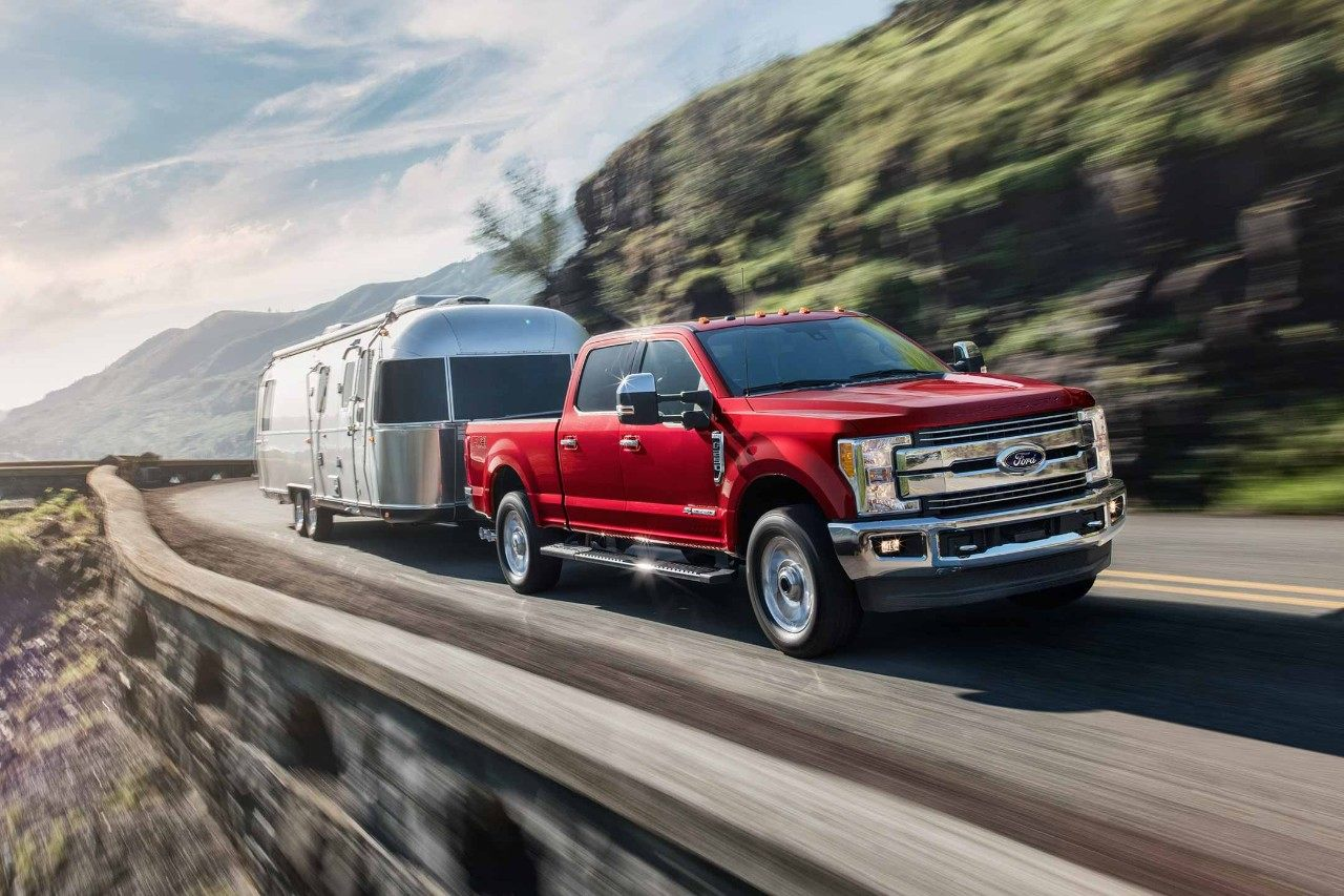 New 2018 Burgundy Ford F250 Pickup Truck Towing a Chrome Camper Over a Mountain Road