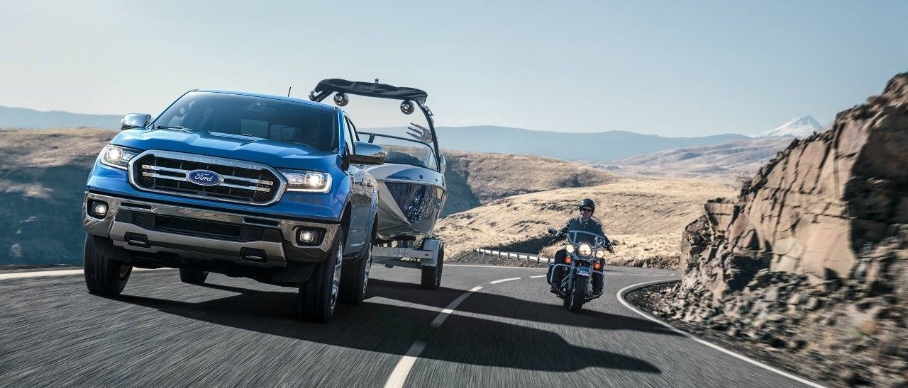 New 2019 Blue Ford Ranger Pickup Truck with Blind Spot Monitor Technology Being Passed by a Motorcycle Rider