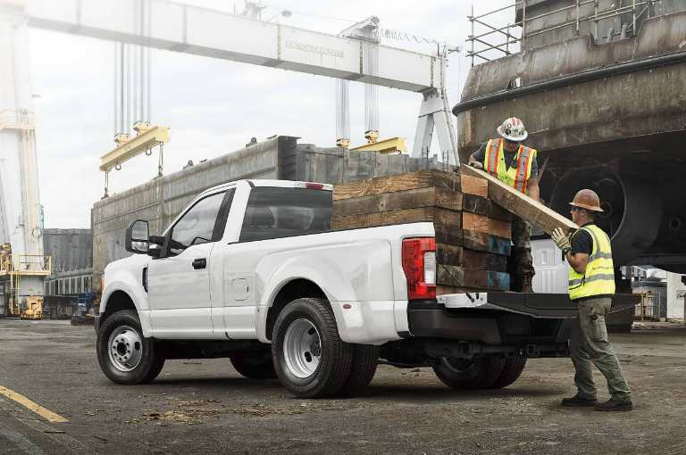 New White Ford Super Duty Pickup Truck with a Full Payload of Logs at a Construction Site