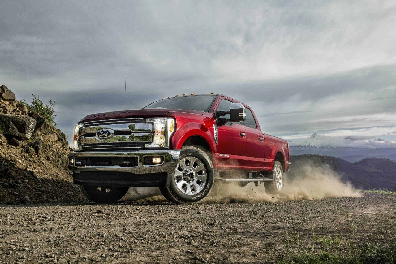 New Burgundy 2018 Ford F250 Pickup Truck Driving Down Gravel Road