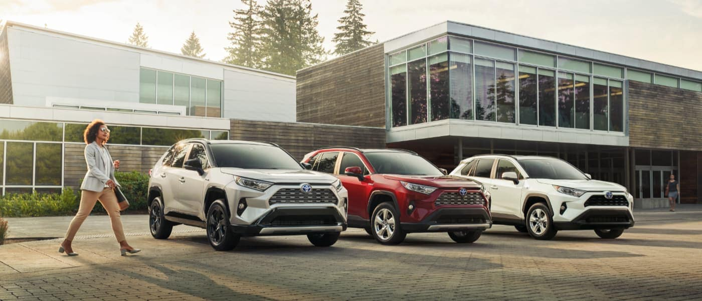 Three Toyota RAV4 Hybrids Parked in Front of a Building