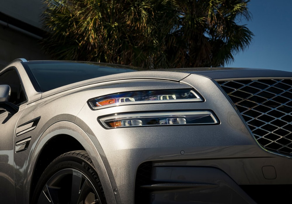 Close up of the front bumper on a 2021 Genesis GV80 showing the unique headlight shapes