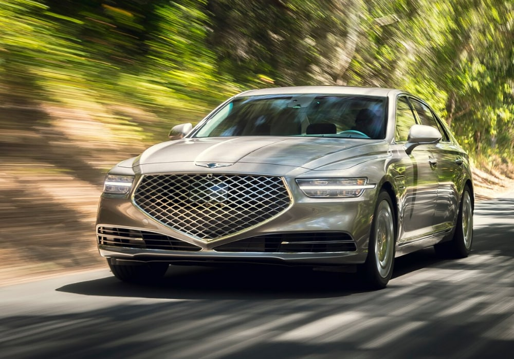 2020 Genesis G90 sedan in gold coast silver color driving down an open road at high speeds