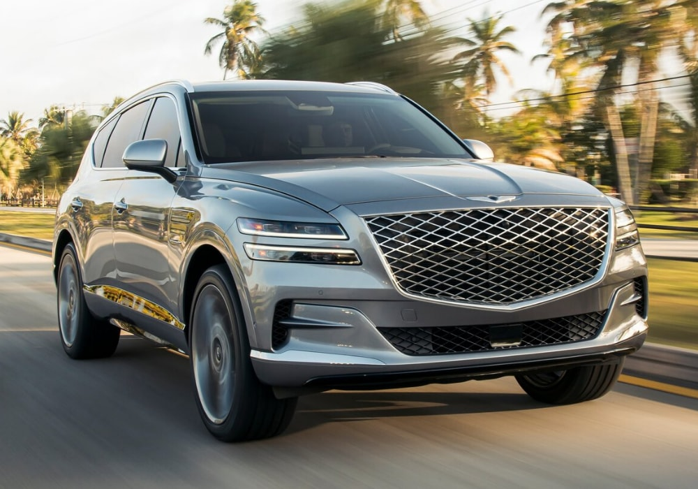 Front exterior design of the first-ever 2021 Genesis GV80 SUV driving down an open city bypass