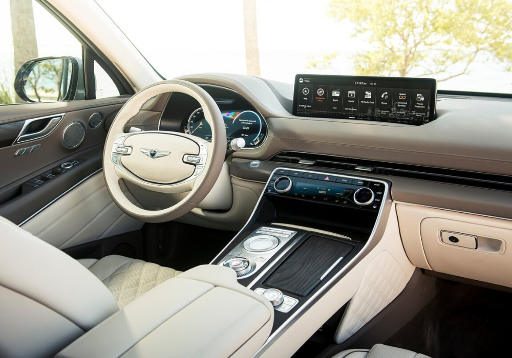 Light-colored, upscale interior front cabin inside the new 2021 Genesis GV80 showing wood grain finished design and diamond-quilted fabric