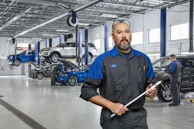 A Ford service technician holding a tool in front of other technicians working on vehicles