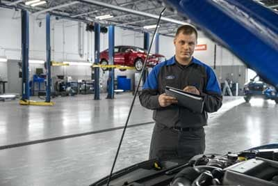 A Ford Auto Body Repair technician going over checks for a Ford Car