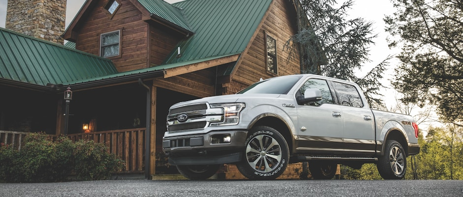 A silver Ford F-150 parked in front of a cabin