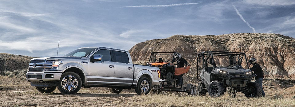 2019 Ford F-150 towing ATV's in field