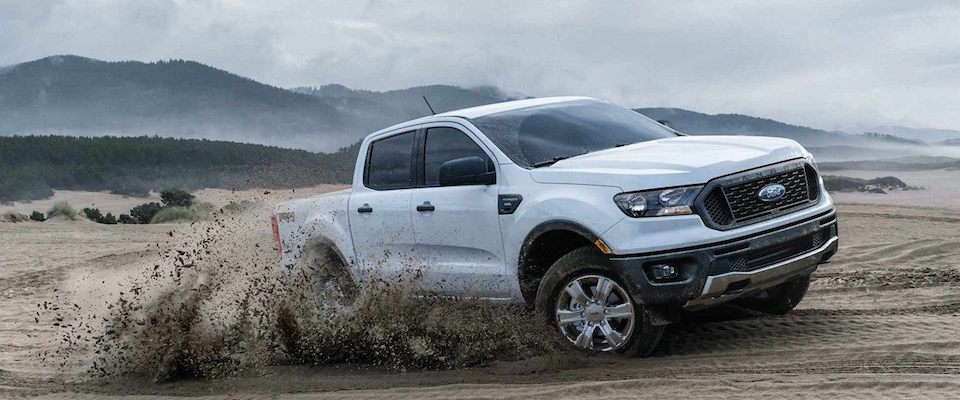A white 2019 Ford Bronco driving through mud