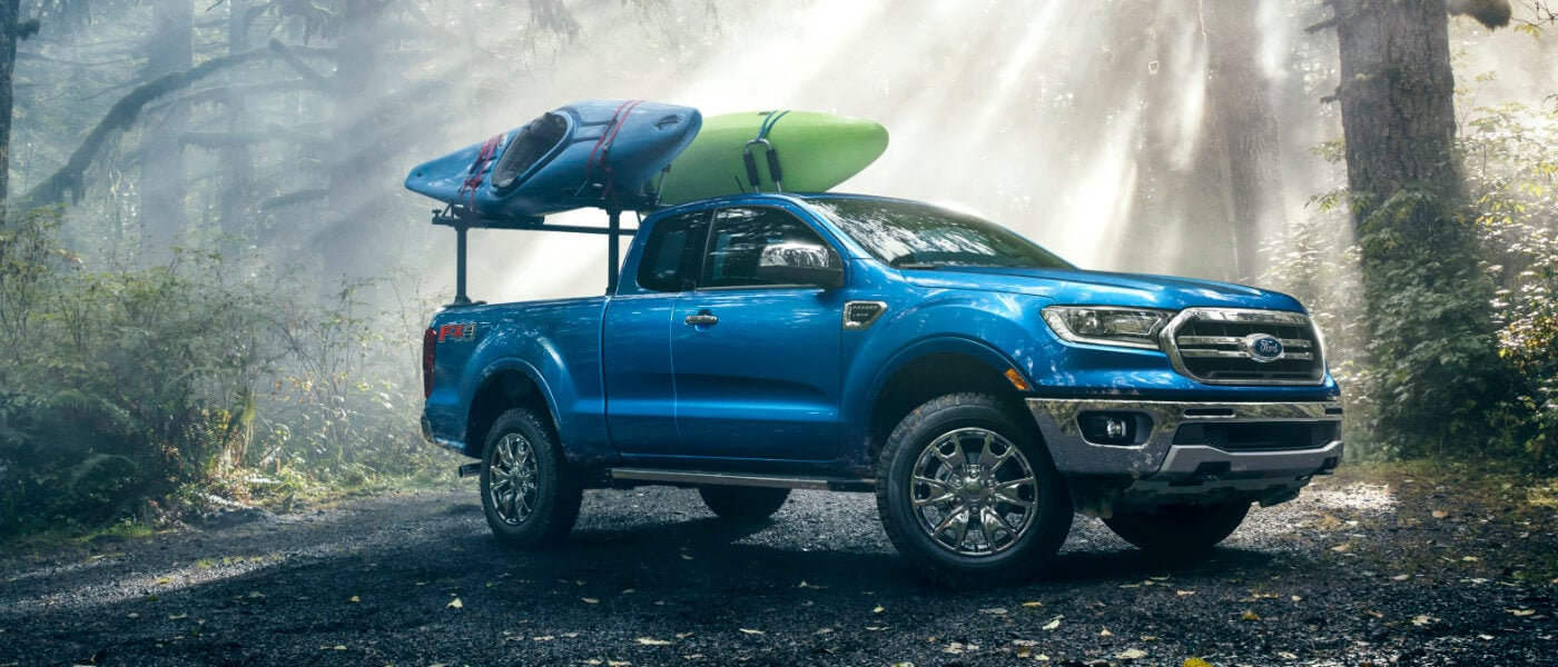20 Ford-Ranger in blue parked in Forest Sunrays shinning onto the vehicle with kyacks on the back