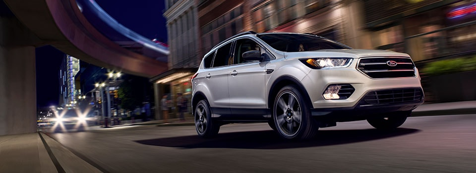 Silver 2019 Ford Escape driving at night through a city
