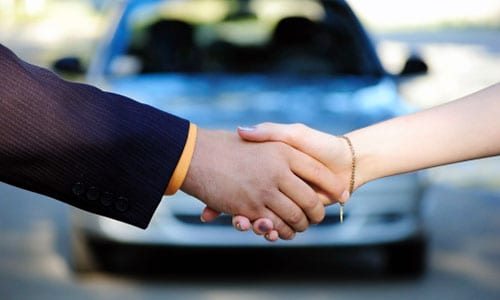Man shaking hands with woman for car deal