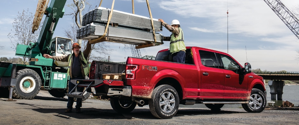Two workers loading up a Ford F-150