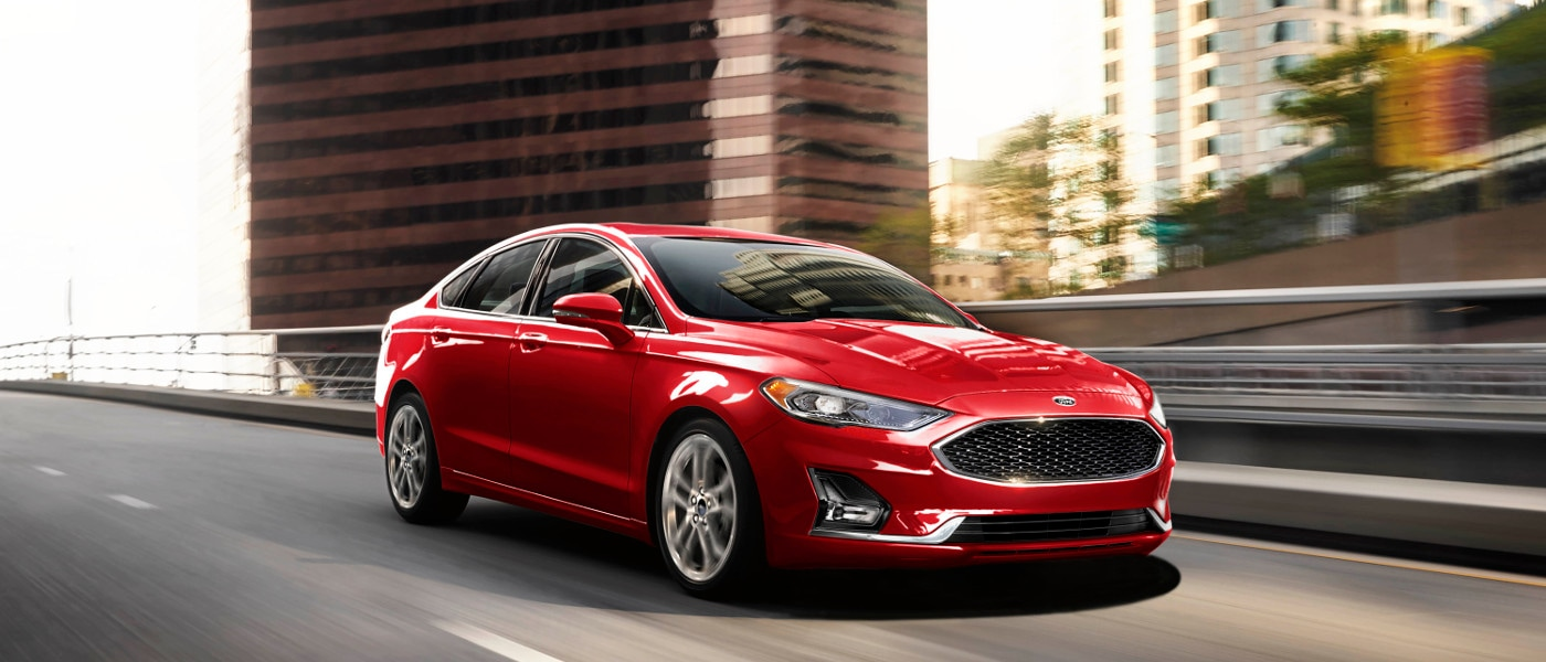 Red 2020 Ford Fusion driving in city