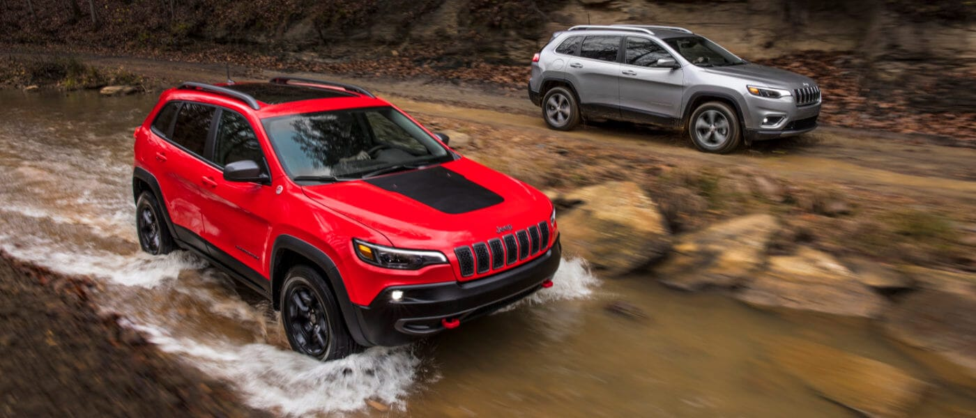 Two Jeep Cherokees driving in the woods by a river
