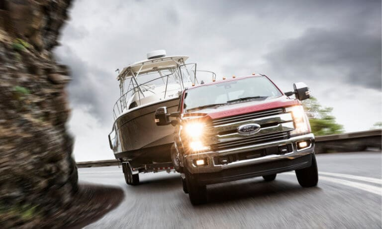 2019 Ford F-250 towing on a rocky highway curve
