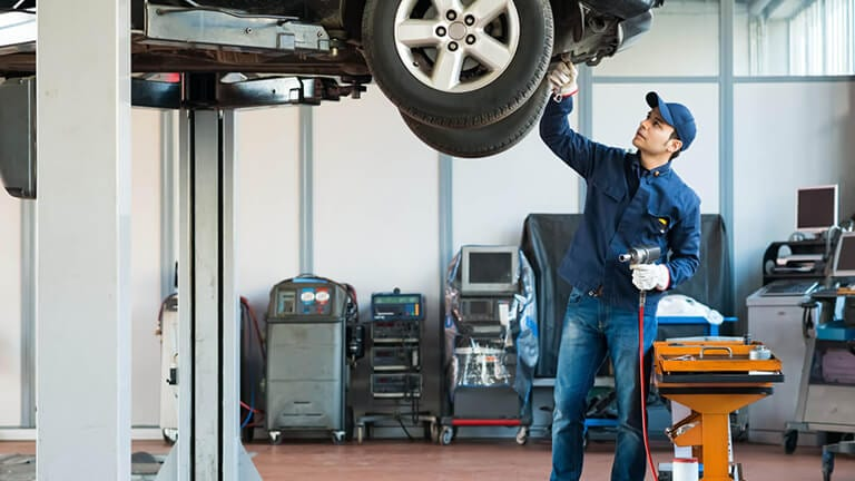 Mechanic inspecting the undercarriage on a lifted vehicle