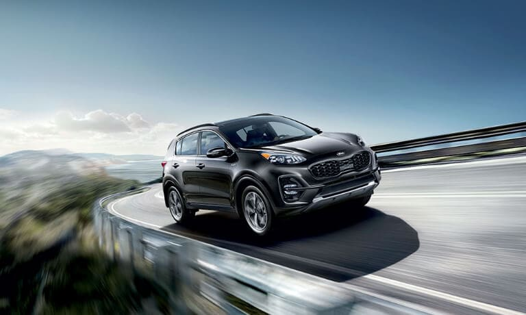 2020 Kia Sportage in black driving on highway driving on the mountian