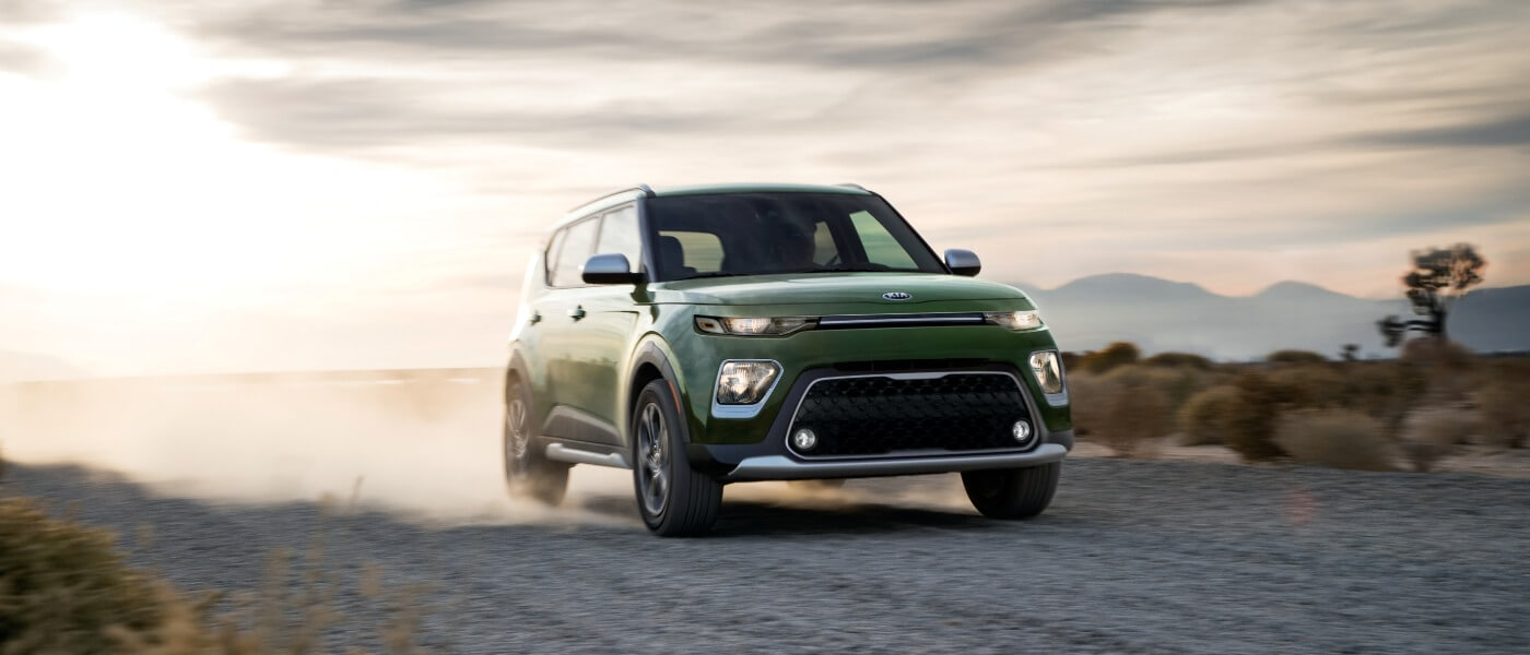 2020 Kia Soul in green exterior driving on a gravel road