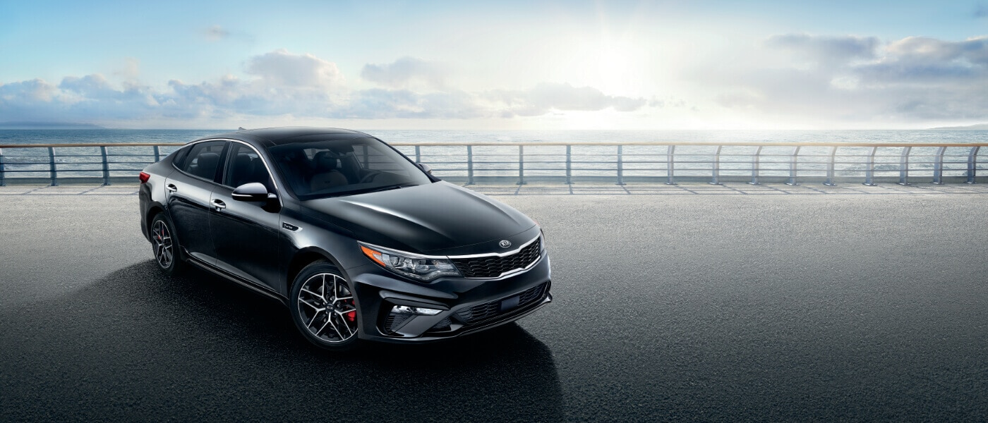 2020 Kia Optima in black parked on a road along the ocean front