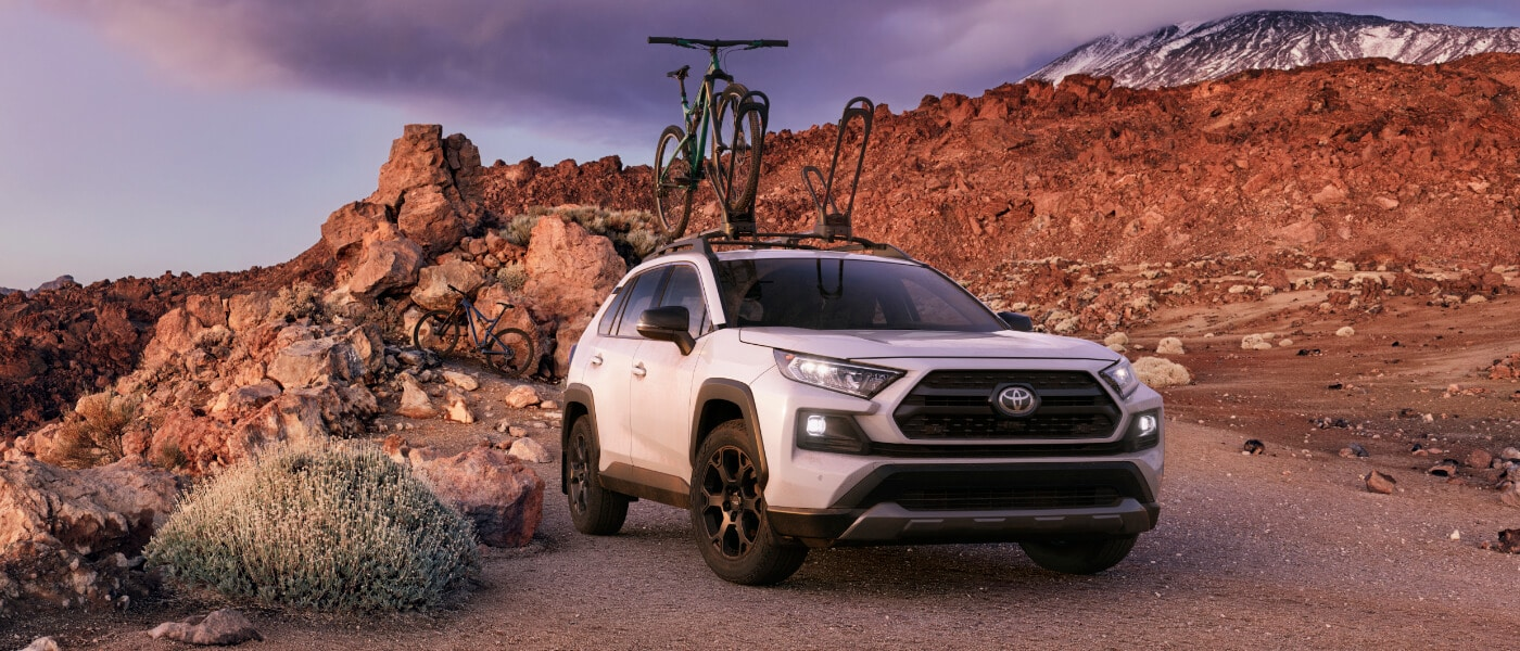 2020 Toyota RAV4 in white with bike racks parked in desert mountians off road during the day