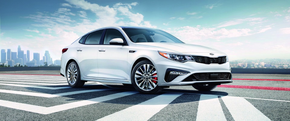 A white 2019 Kia Optima parked on concrete