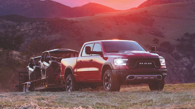 A red Ram 1500 towing ATVs throught the mountains at sunset