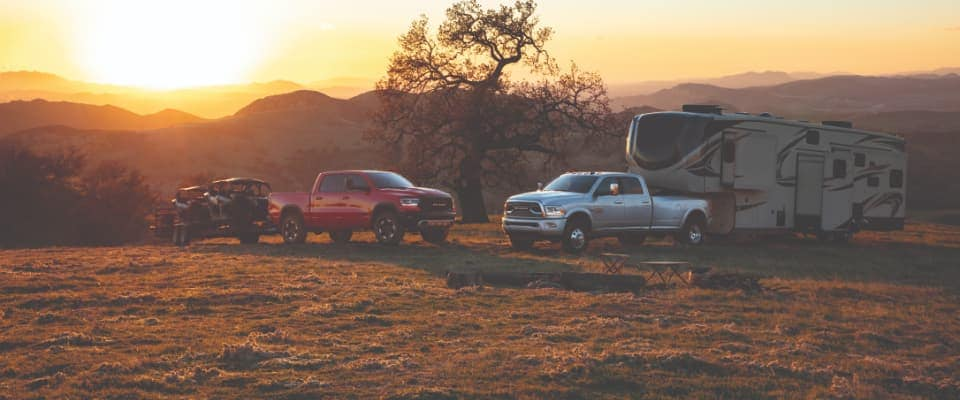 A Ram 1500 & Ram 3500 parked in a field at sunset