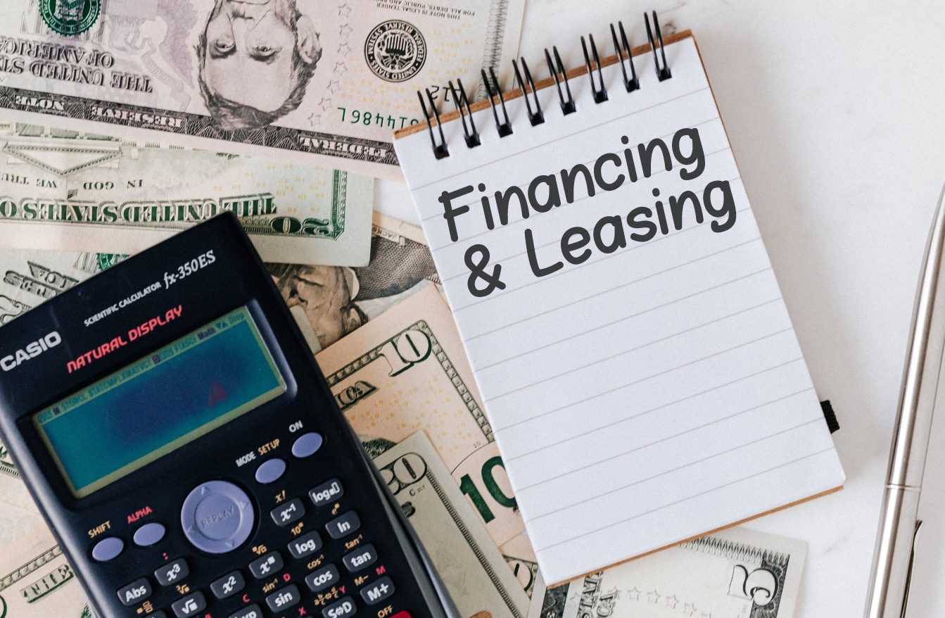 """Calculator on money pile and notebook with """"Financing and Leasing"""""""