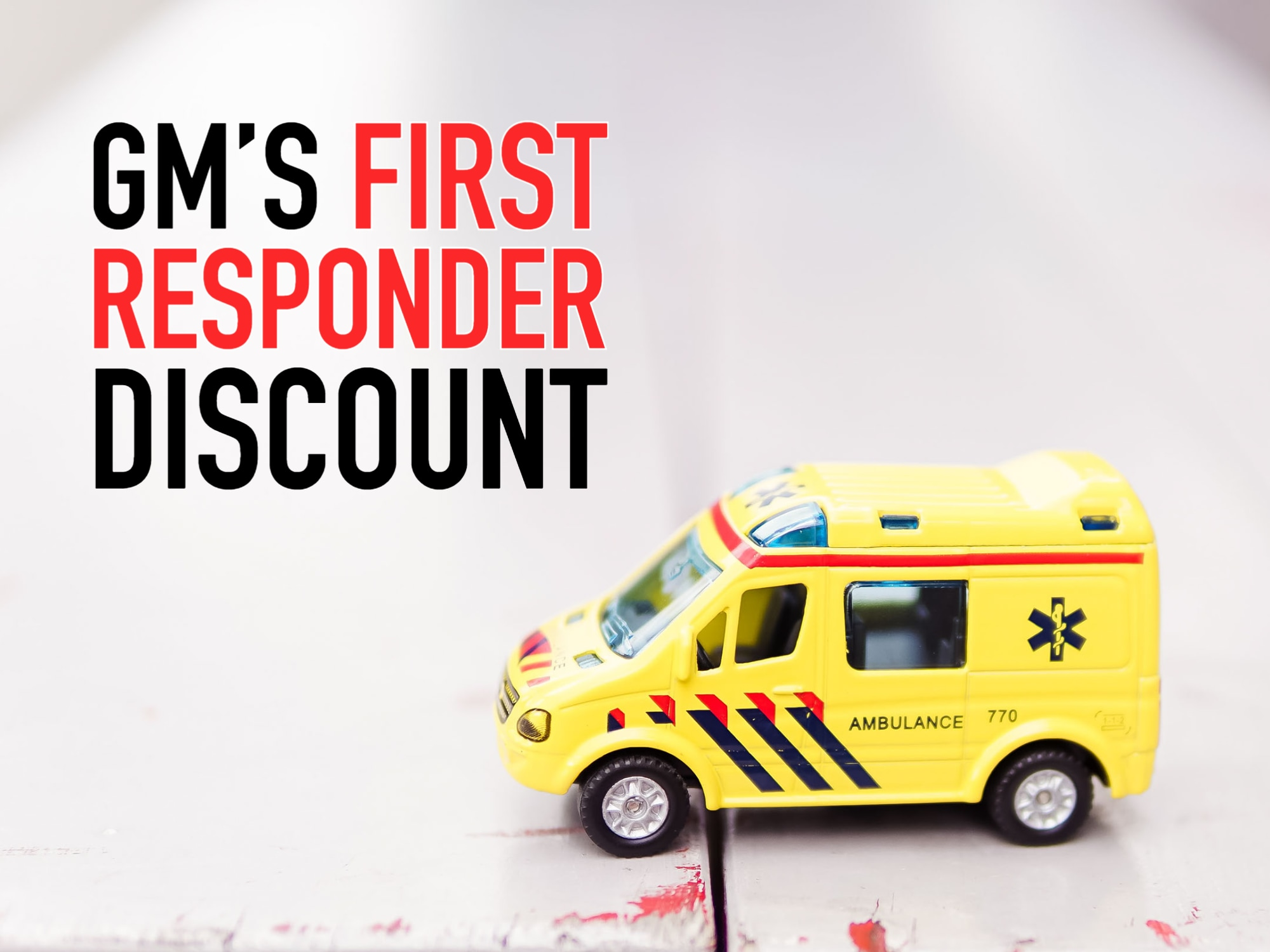 "Small Toy Yellow Ambulance on Table with words ""GM's first responder discount"""