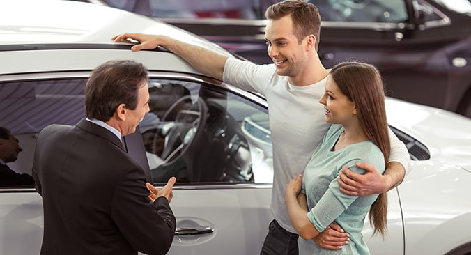 Couple with salesman at the dealership