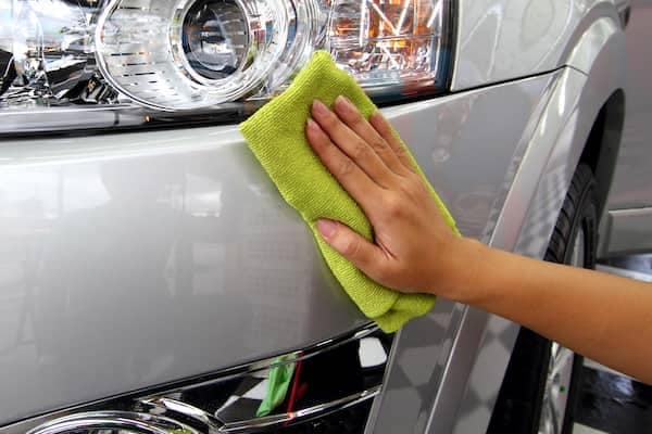 Person with a lime green cleaning cloth polishing the front bumper of a new car