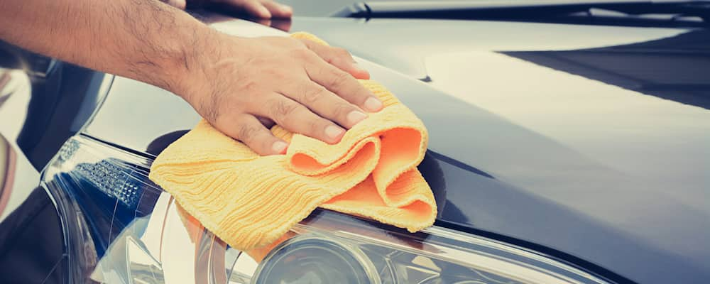 Person wiping headlight off with cloth