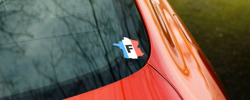 Sticker on car window depicting the country France as an outline, in French flag colors with an F in the middle