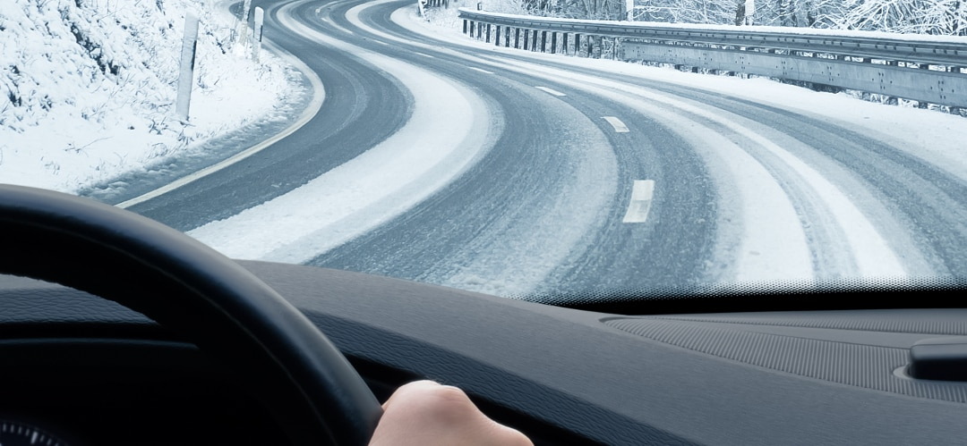 person behind steering wheel of car driving along snowy road