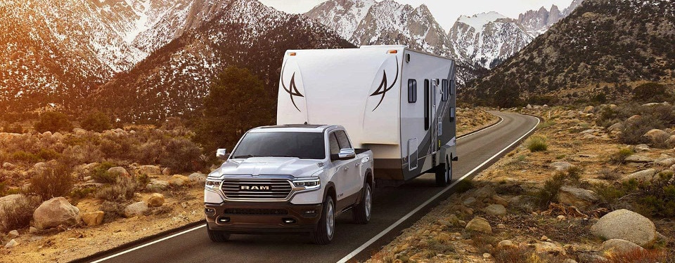 A white 2019 Ram 1500 towing a trailer through the mountains