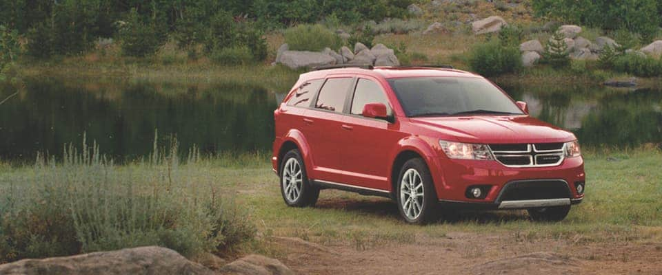 A red Dodge Journey parked near a lake