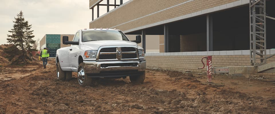 A white Ram 2500 parked in the dirt at a construction site