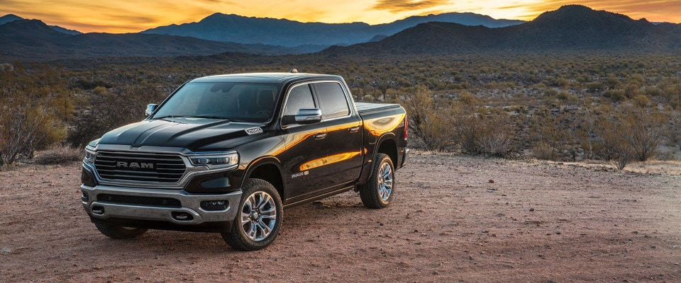 A 2019 Ram 1500 parked in the desert at sunset