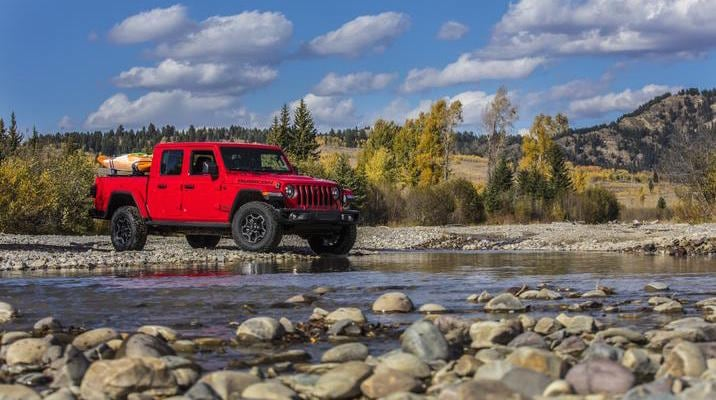 A red 2020 Jeep Gladiator driving near a creek
