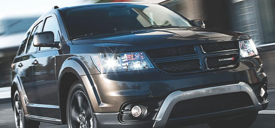 A black Dodge Journey driving down a road